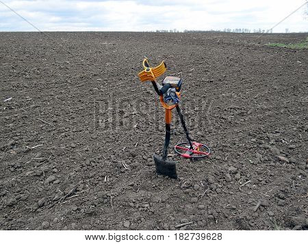 Metal detector on a shovel in a gray box