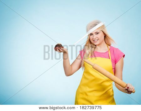 Baking tasty desserts sweets at home concept. Woman holding delicious chocolate cupcake rolling pin wearing apron and colander on head as hat.