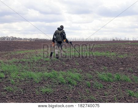 A man with a metal detector and a shovel in his hands looking for finds on a plowed field