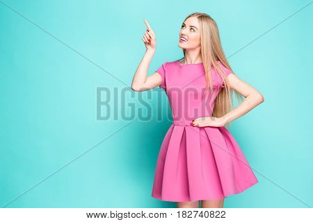 Smiling beautiful young woman in pink mini dress posing, presenting something and looking away. Three quarter length studio shot on blue background.