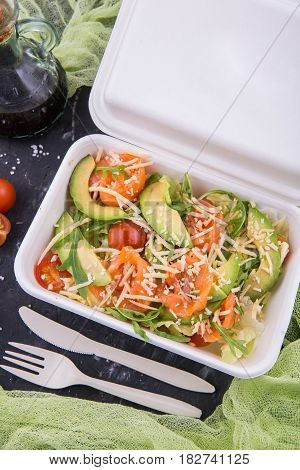 Classical combination of a salmon and avocado to salad iceberg, arugula and cheese parmesan