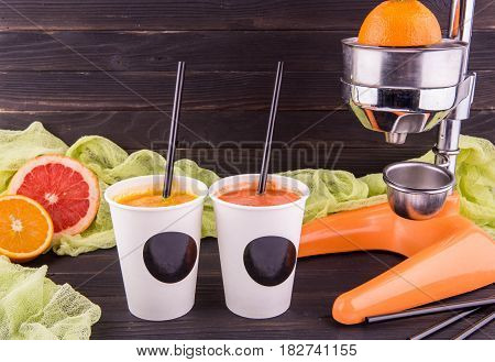 Nonalcoholic juice orange and juice grapefruit in plastic glasses with tubules