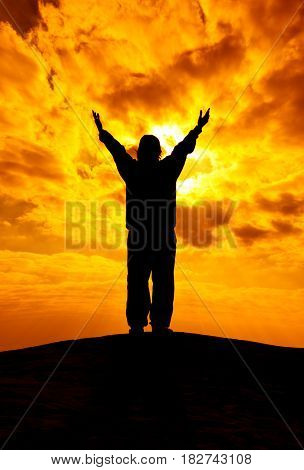 Silhouette Of Woman With Hands Rise Up And Pray With Sunlight. Freedom Concept.
