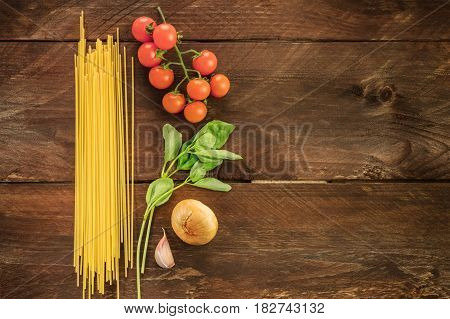 An overhead photo of basic pasta ingredients. Spaghetti, cherry tomatoes, a garlic clove, an onion, and a sprig of basil leaves, on a dark wooden background texture with copy space