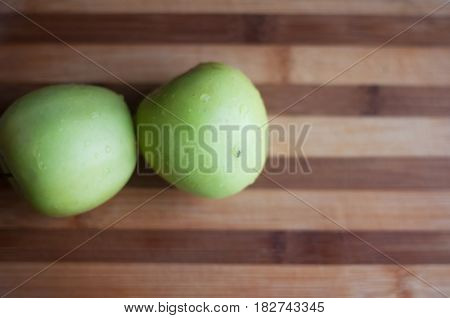 Two green apples lie on wooden cutting board top view with copy space