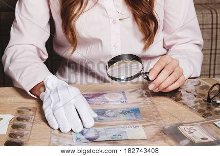 Collectible Coin In The Woman's Hand Through The Magnifying Glass