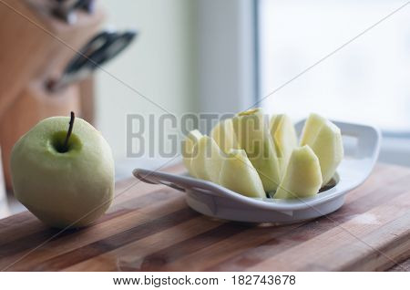 Brushed apple and sliced on wooden cutting board