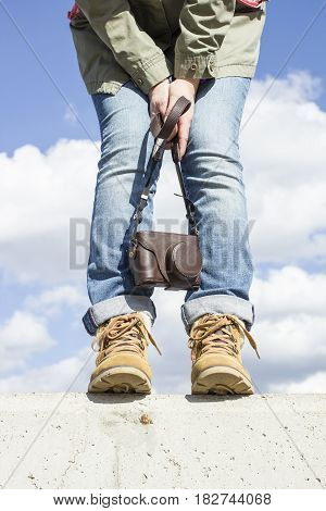 Young woman with feet clad in boots standing on a concrete wall holding a camera in her hands. Against the background of the blue sky and white clouds.