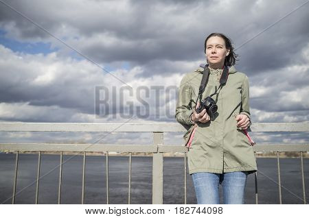 enchanted woman tourist photographer stands with a camera in sunny day on background of water