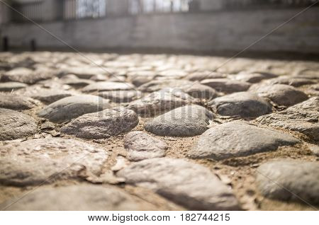 Old cobbled pavement of cobblestones in the city in the background stone wall. Close-up.