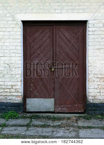 Old Brown wooden door on the white brick wall
