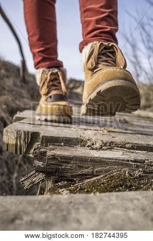 Girl walks along the old rotten wooden bridge in stylish boots on a spring sunny afternoon.