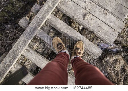 Girl is standing on an old rotten wooden bridge in stylish boots on a spring sunny afternoon. Top view.