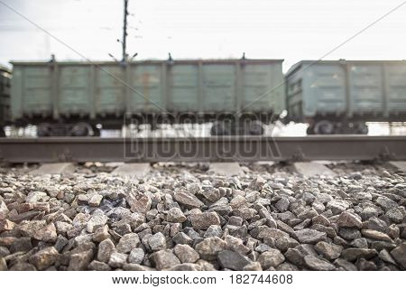 Rails of the electrified railway lie on the rubble in the background freight wagons in the rays of the evening sun.