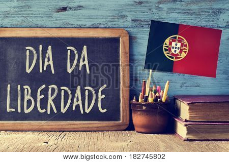 the text Dia da Liberdade, the Day of Freedom national holiday in Portugal written in Portuguese in a chalkboard, and a flag of Portugal, on a rustic wooden table