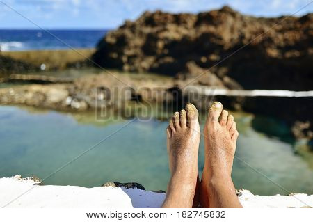 closeup of the bare feet of a young man relaxing in a natural pool of seawater