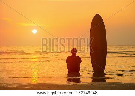 Vacation Concept ; Happy Asian surfer sitting with surfboards on the beach at sunsetPhuketThailand