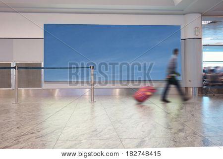 A man with suitcase walks in an airport with blue sky sign behind him for copy space