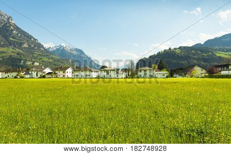 Panorama of the town of Brunnen. Traditional Alpine meadows with luscious bright grass. Travel to Europe.