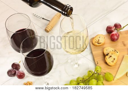 A closeup of white wine poured into a glass at a tasting, with cheese, bread, and grapes. Selective focus