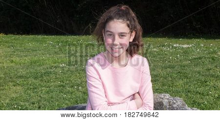 Young Pretty Girl In A Pink Sweatshirt Sitting On A Bench In The Park
