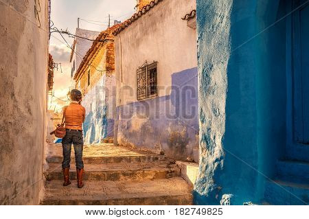 Stylish photographer at famous blue city of Chefchaouen, Morocco.