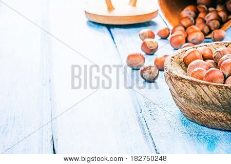 Hazelnuts in shell scattered on blue plank table and in wood bowl