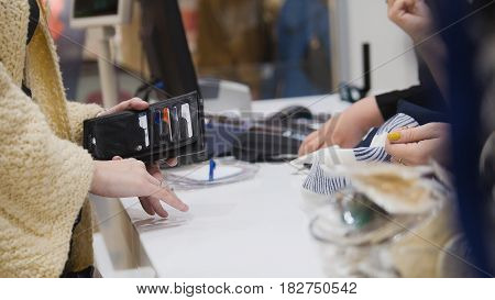 Woman paying by credit card in dress store - shopping concept, close up