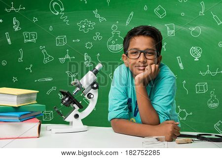 Kids and science concept - cute indian little boy studying science and using microscope with diagrams or doodles drawn over green chalkboard background