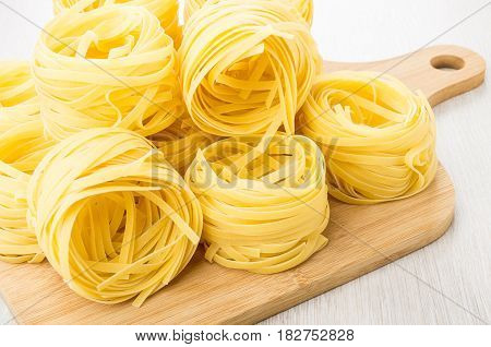 Heap Of Pasta Tagliatelle On Cutting Board On Table