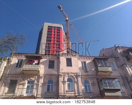 Old two-story house against the blue sky. Behind the house a new bright high-rise building is being built. Construction crane. Concept: old and new, past and present. Spring cityscape.