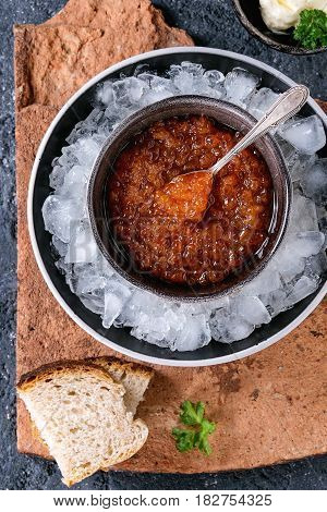 Bowl of red caviar on ice with spoon served with sliced bread, butter and herbs on terracotta board over black stone texture background. Top view, close up