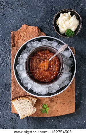 Bowl of red caviar on ice with spoon served with sliced bread, butter and herbs on terracotta board over black stone texture background. Top view with space