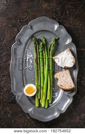 Cooked green asparagus with half boiled egg and sliced bread served with sea salt on vintage metal plate over brown texture background. Top view, fine dining