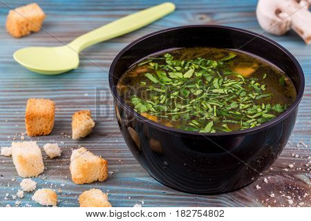Mushroom soup with toasts and greens, is served in plastic ware