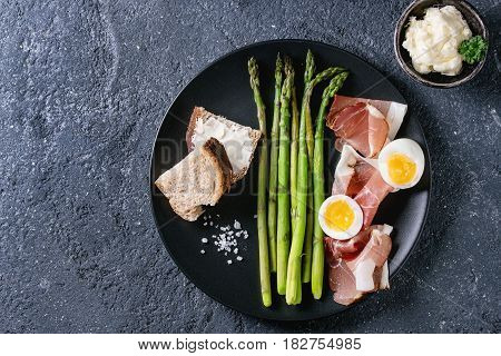 Cooked green asparagus with half boiled egg, sliced bread, butter and ham bacon served with sea salt on black ceramic plate over dark stone texture background. Top view, fine dining