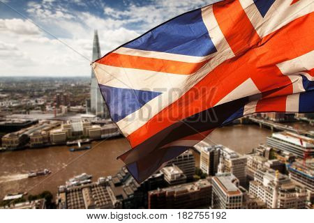 union jack flag over London financial district with iconic skyscrapers, UK prepares for elections after Brexit