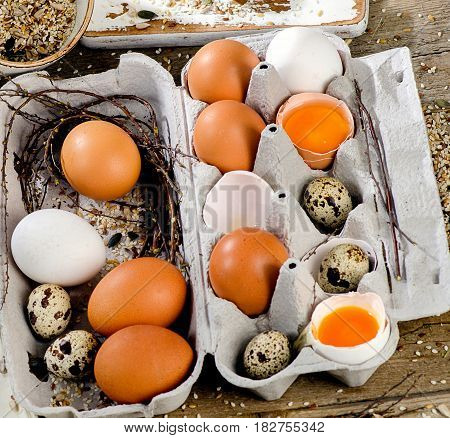 Chicken And Quail Eggs In Egg Box On A Rustic Wooden Background.