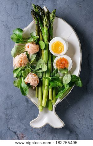 Cooked green asparagus with half boiled egg, salad, red caviar and salmon pate served on white fish shape plate over gray blue texture metal background. Top view, fine dining