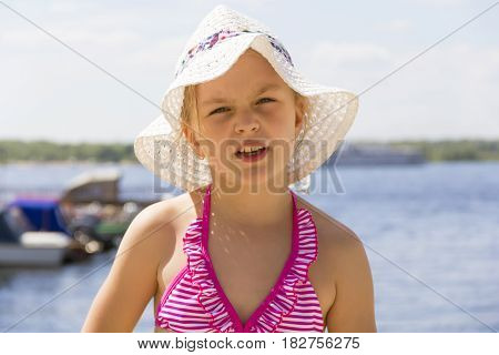 Cute girl in pink swimsuit and white hat