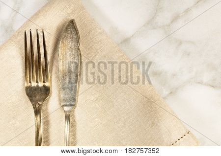 An overhead photo of a vintage fork and knife on a white marble table. A restaurant menu or special offer banner design template