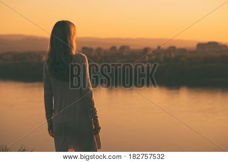 Lonely woman standing and looking at the sunset over the city.