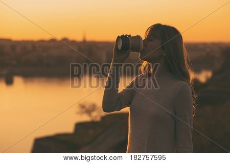 Silhouette of a woman drinking coffee at the sunset.