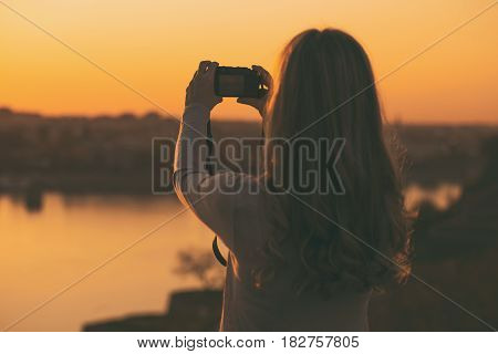 Silhouette of a woman photographing at the sunset.