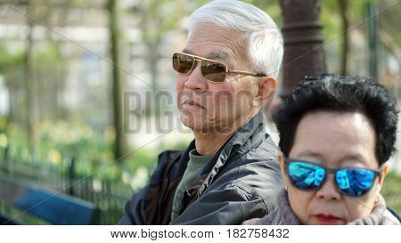 Asian Senior Man Looking Angry At His Wife Through Sunglasses While Traveling