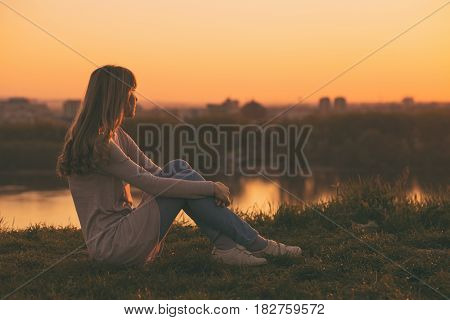 Woman enjoys relaxing and looking at the sunset over the city.
