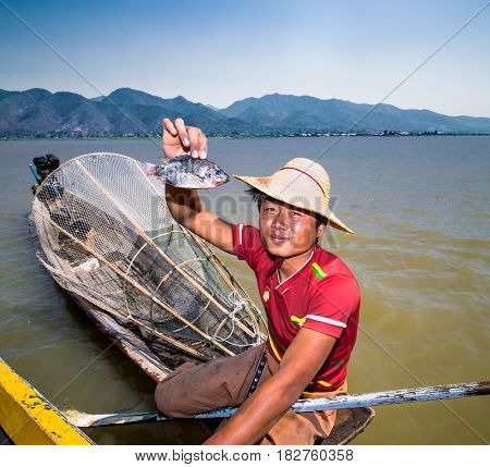 INLE , MYANMAR-MARCH 4, 2017: Burmese fisherman shows tourists hooked fish on Inle lake on March 4, 2017,  Myanmar. (Burma)