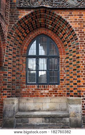 Stone bench and lancet window in brick wall of Old Town Hall in Hannover, Germany.