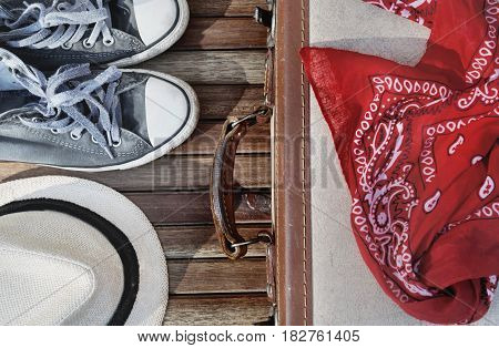 red scarf on a retro suitcase with hat and shoes on wooden background