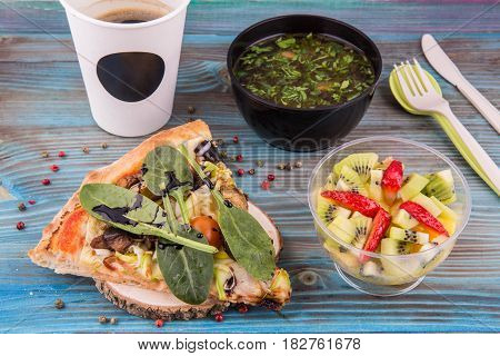 Fast set. Mushrooms soup, piece of vegetable pizza and fruit salad